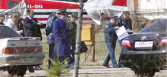 Sergei Shoigu approaches the airport fence perimeter, behind which are the remains of the Polish government Tupolev Tu-154M plane. (Behind Mr. Shoigu, we can see a Spetsnaz officer who is putting away a cell phone in his jacket pocket).