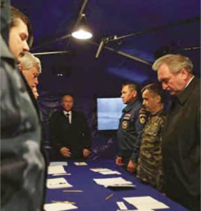 "April 10, 2010, Smolensk, Crash Site: ""Staff Briefing"" in a tent. From the right: Sergei Antufiev - Governor of the Smolensk Oblast, Rashid Nurgaliyev - (Spetsnaz) Army General, Mikhail Osipienko, Supreme Commander of the RF Ministry for Extraordinary Emergencies, Smolensk District, and Vladimir Vladimirovich Putin - then Prime Minister of Russian Federation."
